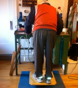 Tank stands at a desk on a balance board, checking the computer.