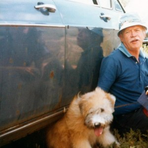 Tank, sitting on the ground, leans against the side of an old blue sedan, his Irish wheaten terrier puppy at his side.