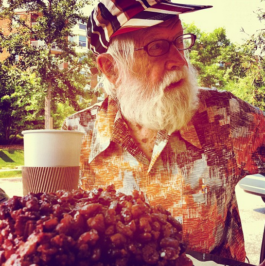 Tank wears an abstract pattern vintage polyester shirt in shades of white, dark brown, and orange., with a striped cap. He's smiling and looking to the side. In front of him is a cup of coffee and in the foreground, a giant cinnamon roll covered with chopped pecans. He's sitting outside, trees in the background.