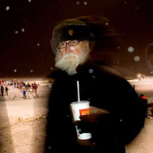 Tank holds a paper cup with straw while wearing a thick black winter coat and large trapper hat with ear flaps. He stares into the camera with a slightly disgruntled expression. Behind him, children play on a frozen lake against a black night sky. In the foreground are blurry snowflakes.