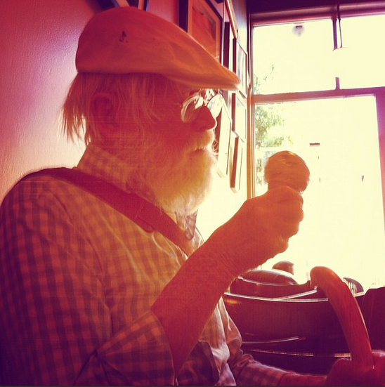 Tank wears a khaki cap and blue and white checked cotton shirt, cuffs folded back, leather messenger bag slung crossbody. He sits in front of a window with bright light streaming in, contemplating his ice cream cone.