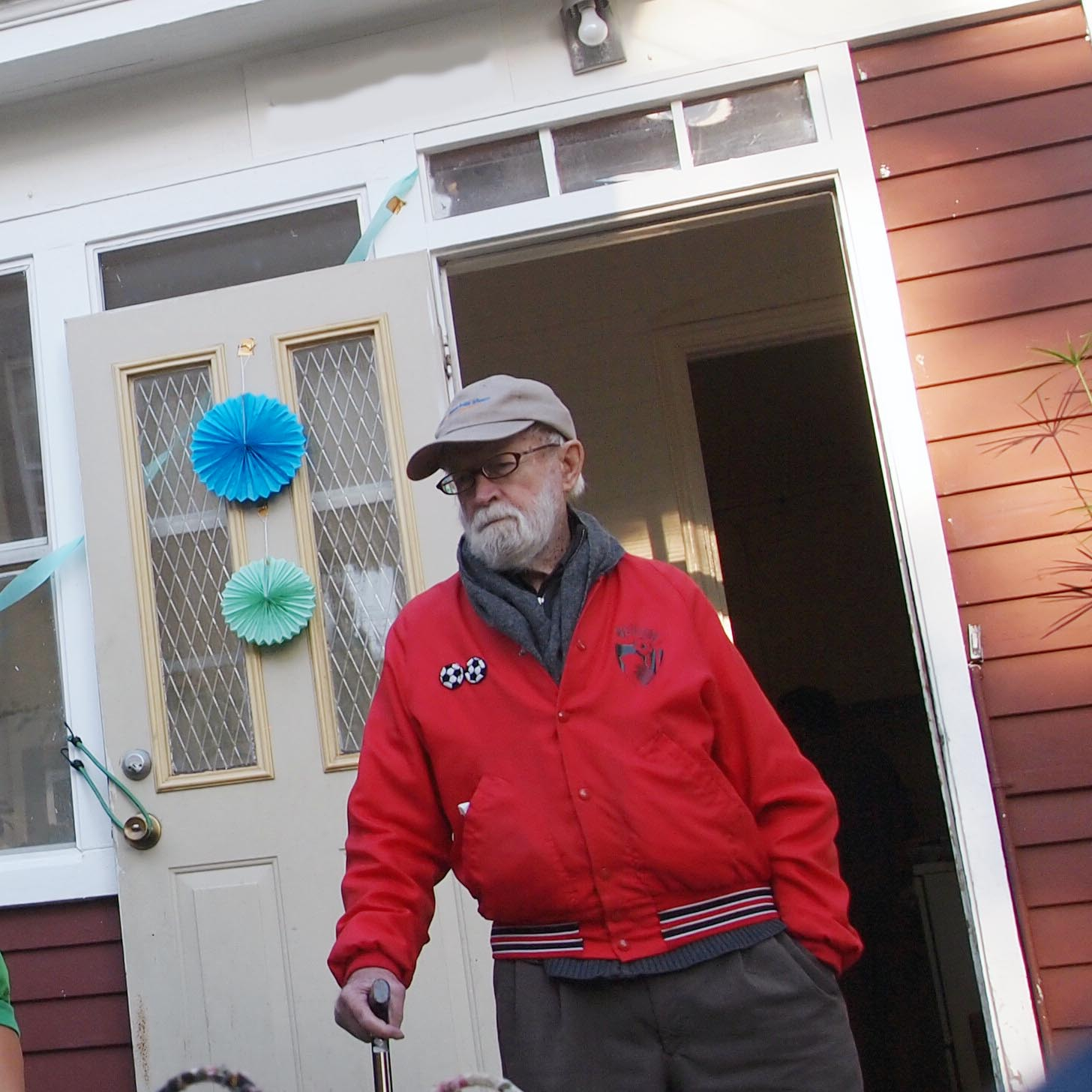 Tank wears a red soccer warm-up jacket, grey scarf, and baseball cap. He leans on the cane in his right hand just outside the open door of a house festooned with decorations.