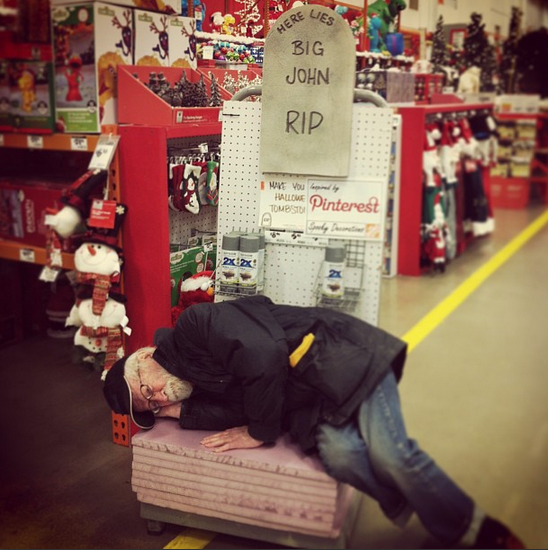 Tank lies down on his side on a pile of foam boards beneath a mock headstone in a big box home improvement store.
