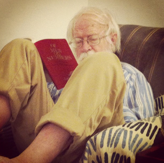 Tank is half curled, half reclined on a well-worn easy chair with dusty blue striped ticking and a hash-marked throw covering the arm. He's barefooted, wearing khakis and a blue striped Oxford while reading.