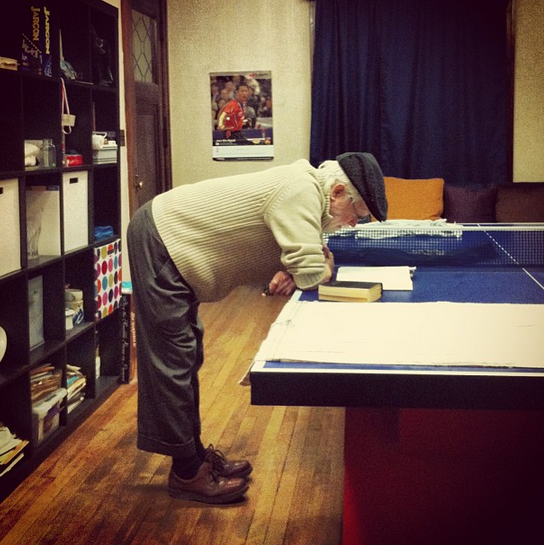 Tank is photographed from the side, in cap, trousers, and cardigan, with brown leather shoes on. He is intently reading. He stands with his legs straight and his torso nearly perpendicular to the ground, his arms braced on a stiga table tennis table as he reads intently. Behind him is an Ikea expedit.