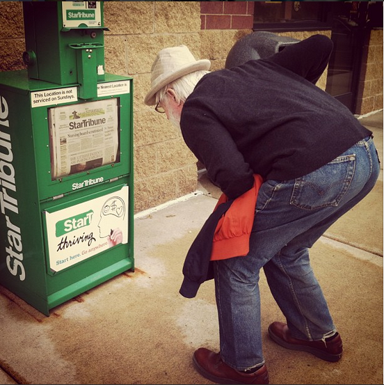 Tank bends over to get a good look at the headlines in the Minneapolis Star Tribune newspaper box. He wears a dapper hat, a dark gray sweater, jeans, and brown leather shoes. He's holding his orange and gray light spring jacket.