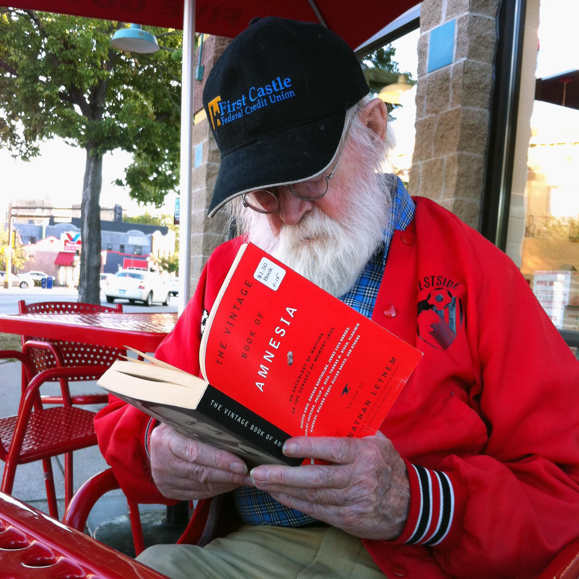 Tank sits at a red iron table outside, wearing a black baseball cap and a red windbreaker, engrossed in a red-covered book with a black spine.