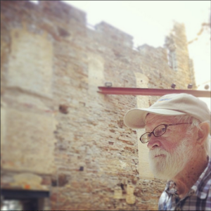 Tank, in a khaki/cream cap and plaid button down shirt, around him in the ruins of the Minneapolis Mill City museum, on the west bank of the Mississippi River.