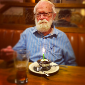 Tank smiling at the camera, sitting at the table with a beer, ice cream with chocolate sauce, and a lit birthday candle, wearing a blue button down shirt.