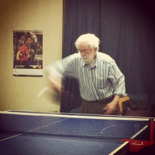 Tank in action at the ping pong table, paddle and ball a blur in his right hand.