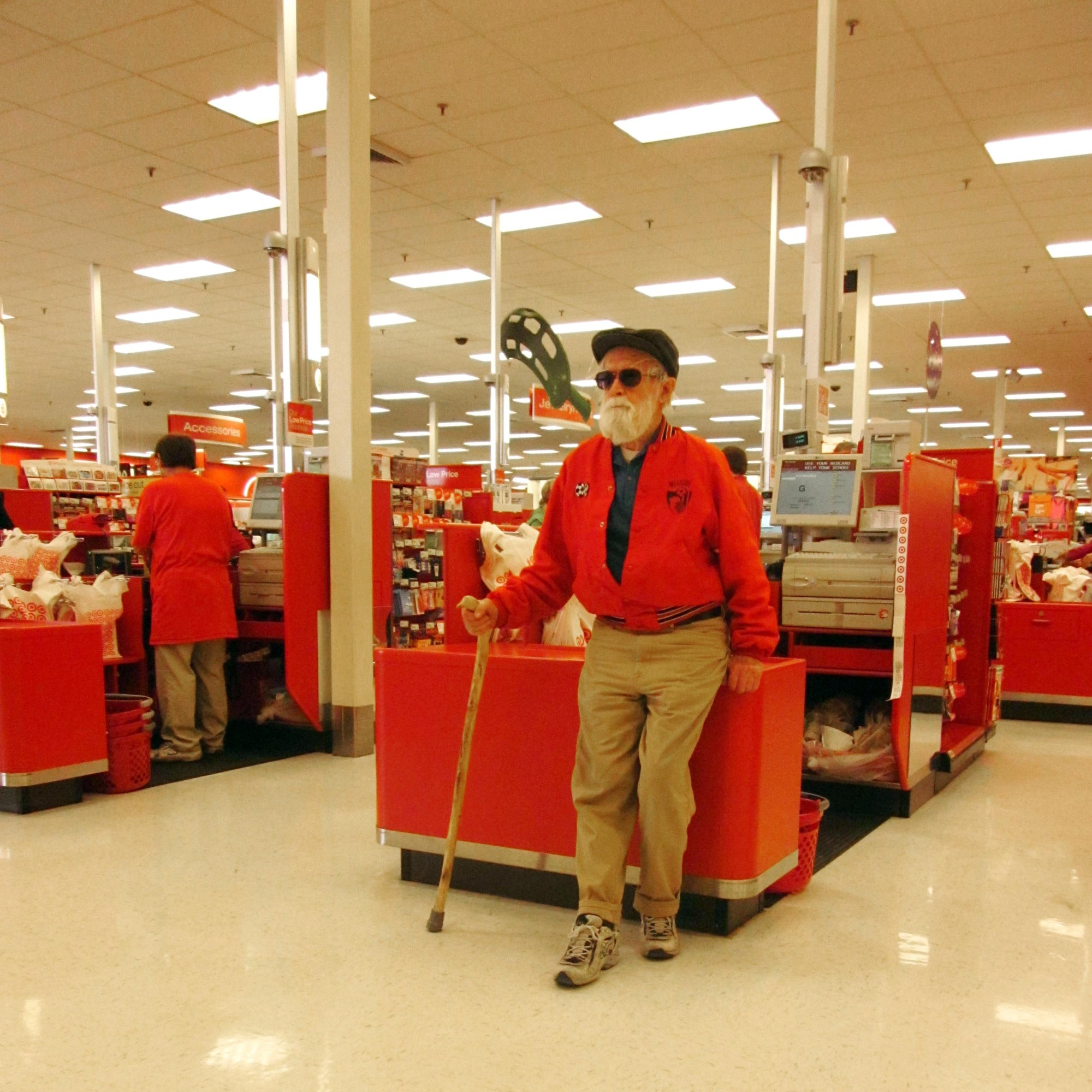 Tank leans casually against an unused checkout desk at Target beneath florescent lights that disappear into the horizon. He's wearing a bright red jacket, half unsnapped, and khaki pants with tennis shoes. He's bearded, wearing sunglasses. He's holding his handcarved stick and wearing a newsboy cap.
