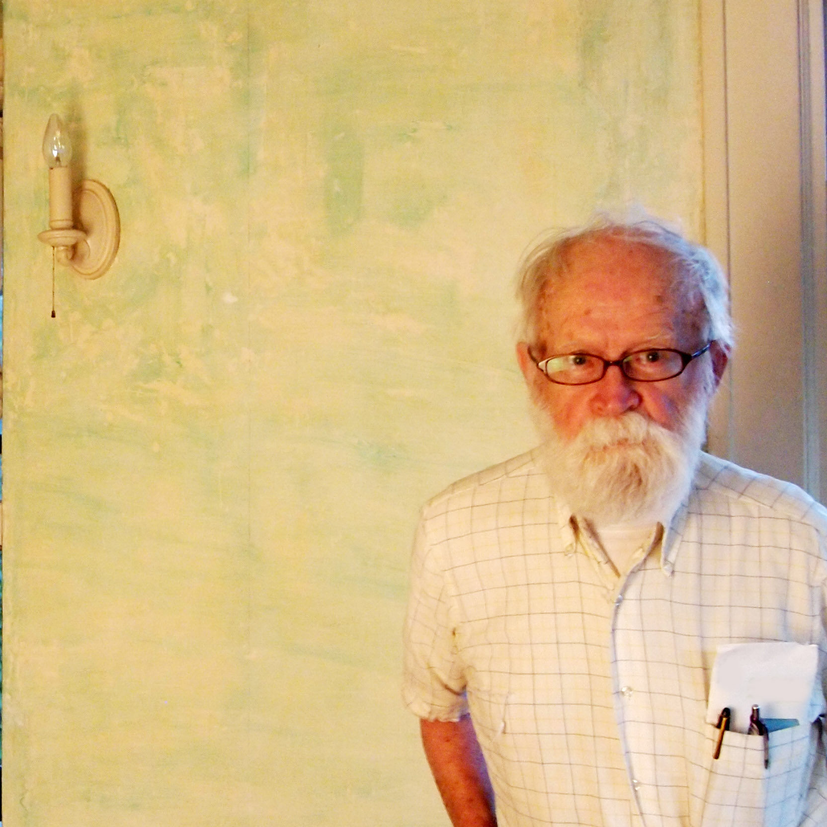 Tank stands in front of an unpainted plaster wall, looking stern. He's wearing a short sleeve cotton button down, pens and envelope in breast pocket, with his hands in his back pocket.