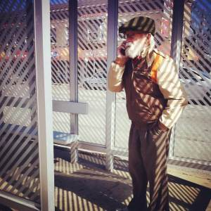 Tank stands in a bus shelter talking on his cell phone, with the partially opaque stripes on the shelter's glass creating shadows across him and the sidewalk.
