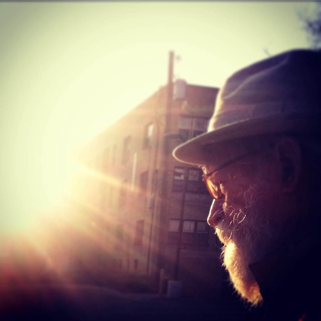 Tank, wearing his dapper cap, walks in the city, the sun illuminating his profile